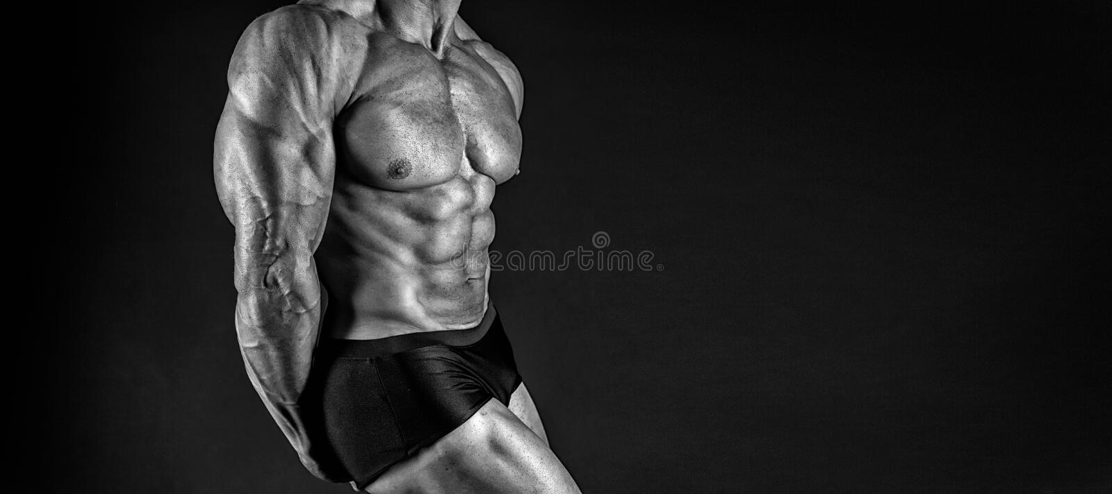 Protein supplements. Muscles for actions. Torso six packs attractive black background. Muscular torso huge muscles. Result of exhausting trainings and proper royalty free stock photo