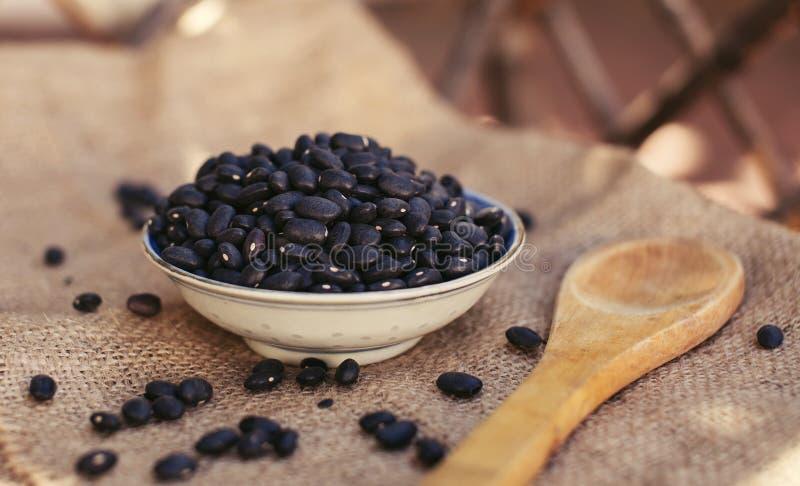 Proteina naturale organica dei fagioli neri con il cucchiaio di legno immagine stock