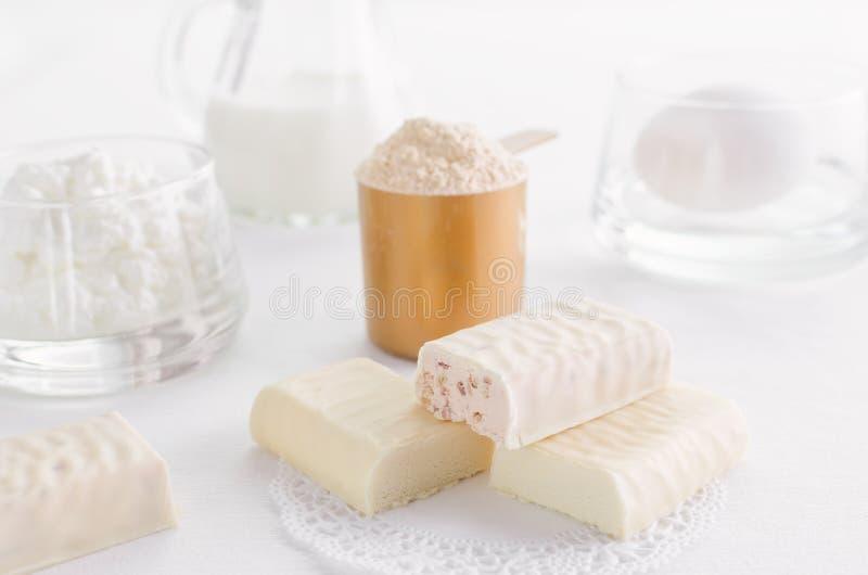 Proteinprodukter liksom vasslapulver, mellanmålstång och ägget med mjölkar och ostmassa royaltyfria foton