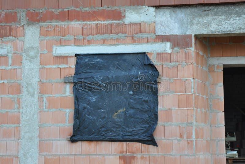 Proteja la casa inacabada Windows para que el invierno evite nieve y la lluvia dentro Reduzca la condensación en el edificio inac fotografía de archivo libre de regalías