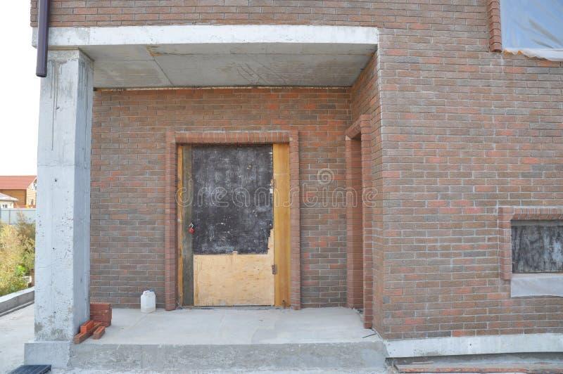 Proteja la puerta y las ventanas inacabadas de entrada de la casa para que el invierno evite el interior de la nieve y de la lluv imágenes de archivo libres de regalías
