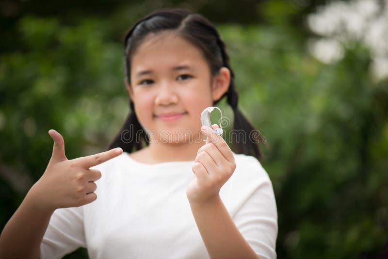 Protesi acustica asiatica della tenuta della ragazza fotografie stock libere da diritti