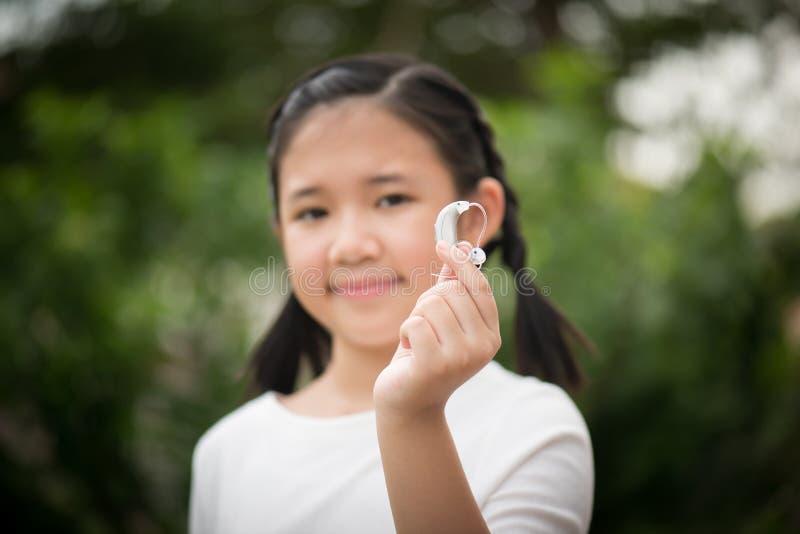 Protesi acustica asiatica della tenuta della ragazza fotografia stock