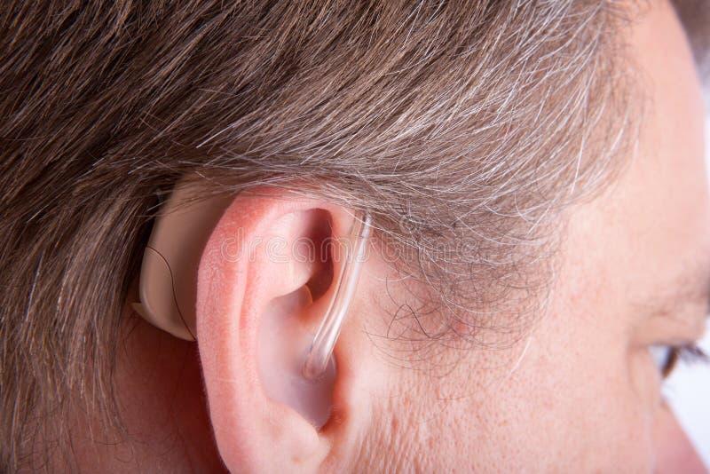 Protesi acustica d'uso dell'orecchio dell'uomo senior immagini stock libere da diritti