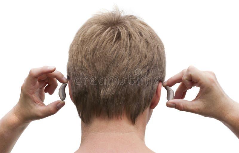 protesi acustica dell'Dietro--orecchio che mette sopra immagini stock libere da diritti