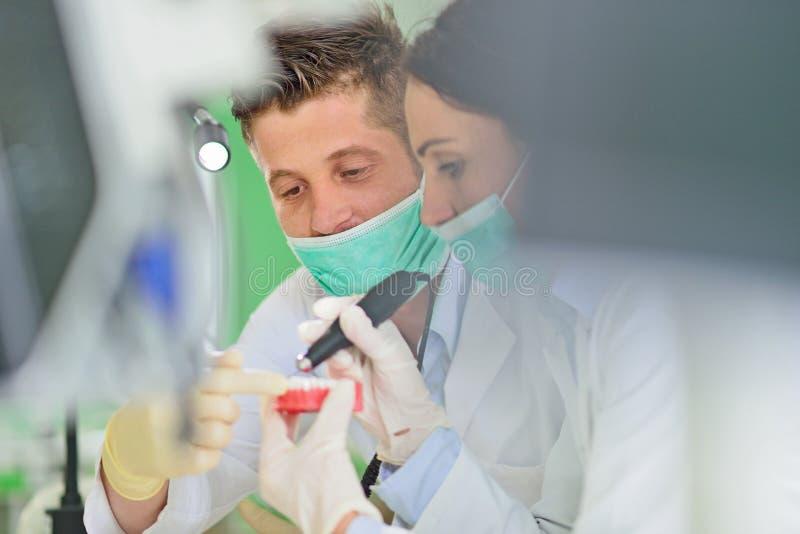 Protesi dentaria, protesi dentarie, attività di protesi Mani di protesi mentre lavorando alla protesi dentaria immagini stock