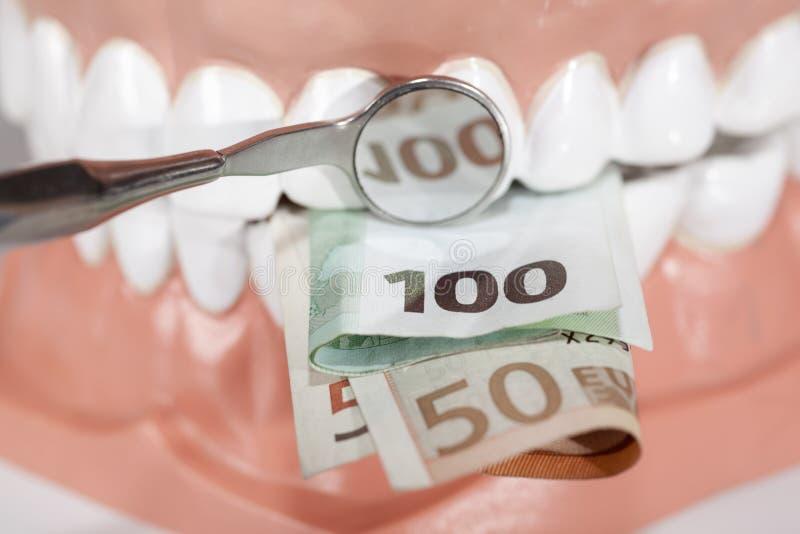 Protesi dentarie che mordono le euro banconote vicino su immagine stock