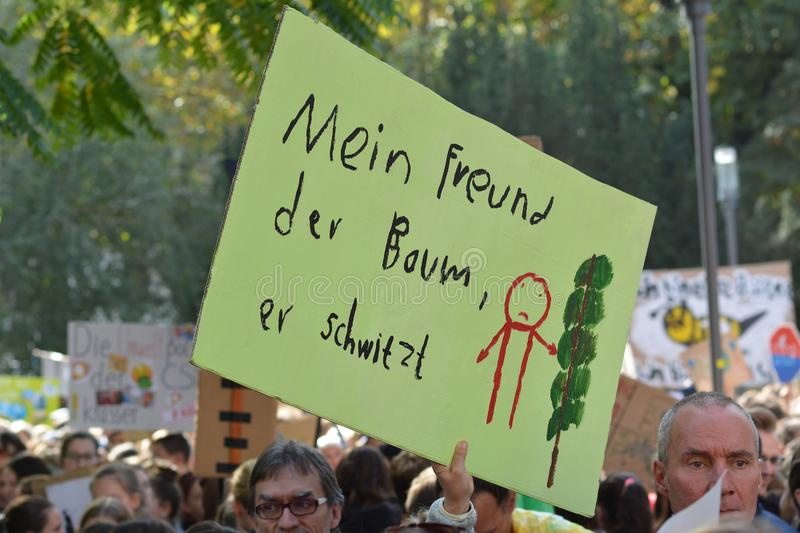 Protest sign cardboard saying `my friend, the tree, is sweating` in German during Fridays for Future strike royalty free stock images