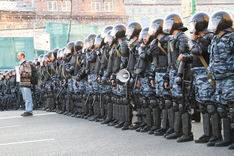 Protestador desconhecido com um cartaz no fundo dos graus da polícia foto de stock