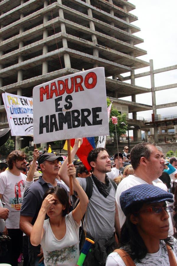 Protestadores antigovernamentais que guardam uma bandeira que leia: MADURO ESTÁ COM FOME imagens de stock