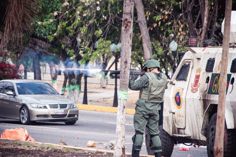 Protestadores do tiro do soldado na Venezuela fotografia de stock royalty free