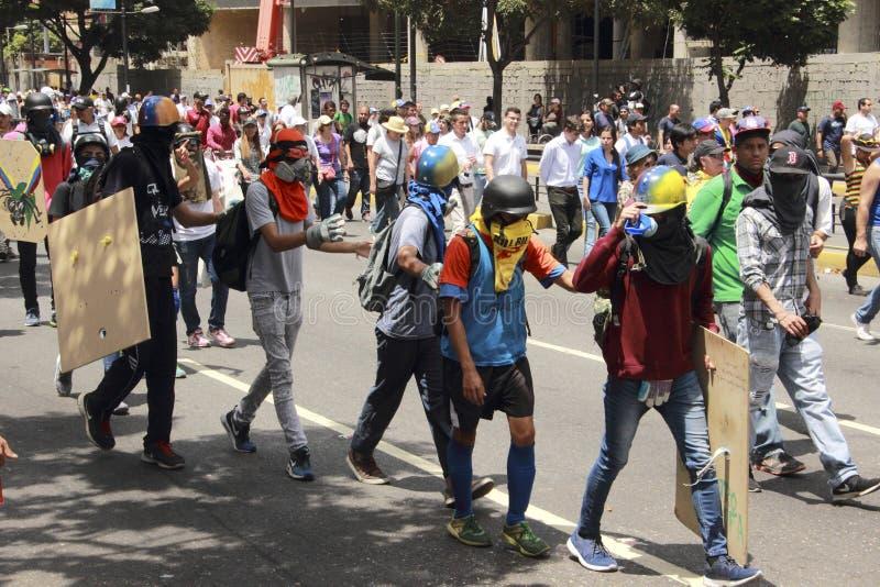 Protestadores na Venezuela de Caracas que indica anti máscaras do teargas fotografia de stock royalty free
