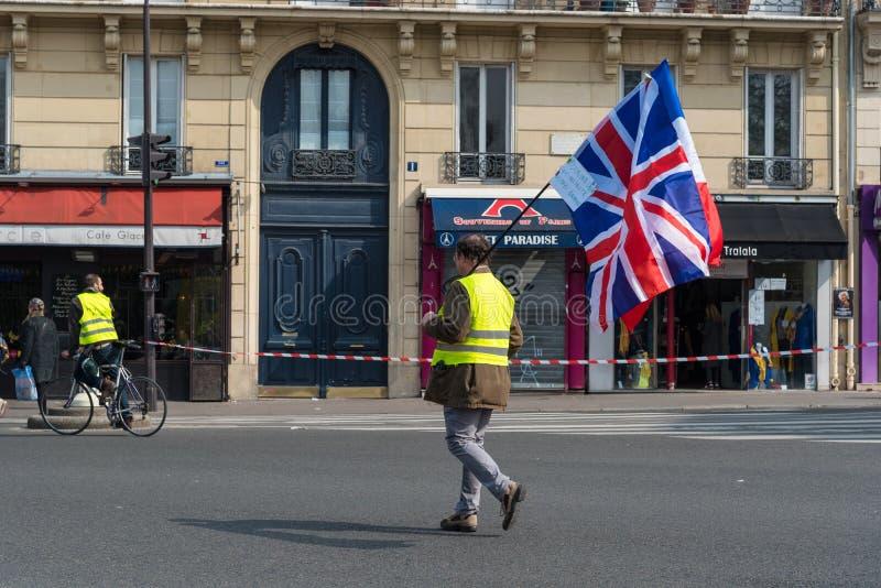 Protestataire jaune de jaunes de Gilets de gilets avec le drapeau du R-U à Paris, France photographie stock libre de droits