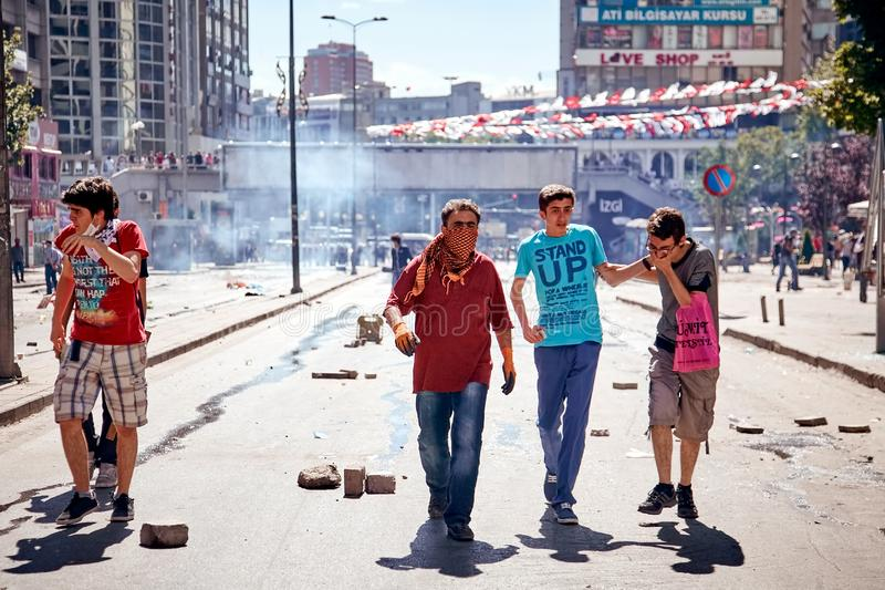 Protestataires affectés par la larme à gaz par la police marchant sur la rue et essayant de s'aider pendant le parc de Gezi photographie stock libre de droits