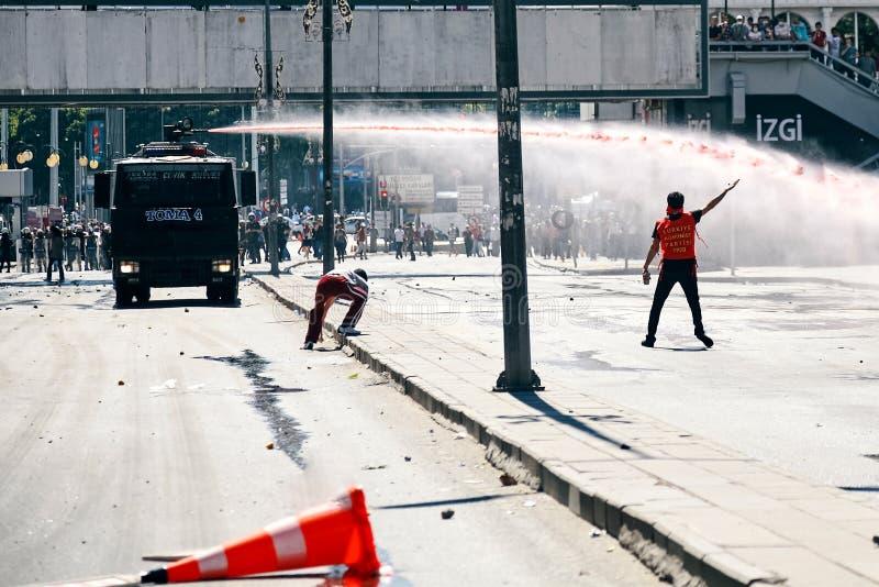 Protestataires essayant de se tenir contre le canon à eau de police tandis qu'il tire le courant de vitesse élevée d'eau pendant  image libre de droits
