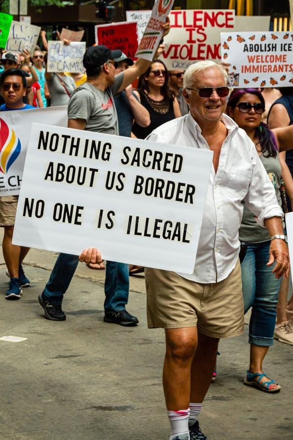 """Protestation contre des centres de détention de patrouille de GLACE et de frontière Un homme porte un signe qui ne lit """"rien sacr photos libres de droits"""