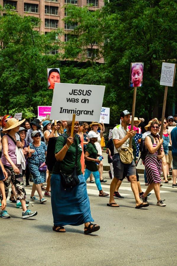 """Protestation contre des centres de détention de patrouille de GLACE et de frontière Une femme porte un signe qui lit """"Jésus était image libre de droits"""