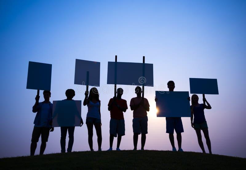 Protesteerder met Uithangbord in Achterlit stock afbeeldingen