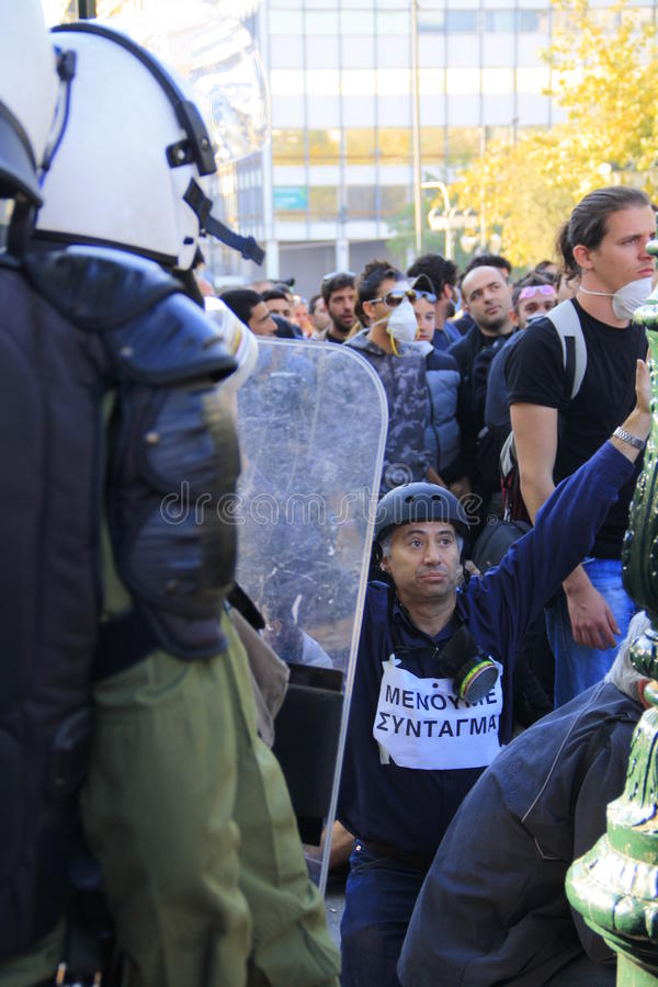 Protesteerder op knieën voor politieagenten stock foto