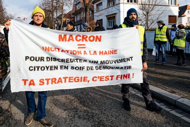 Protesteerders die met aanplakbiljetten tegen Emmanuel Macron lopen royalty-vrije stock afbeelding