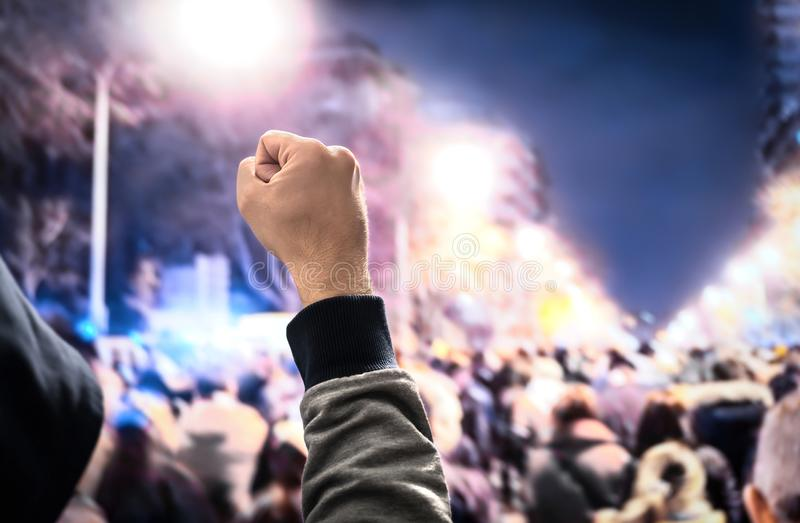 Protesten uppror, marscherar eller slaget i stadsgata Folkmassa av att marschera för folk Med huva man som protesterar näven upp  royaltyfria bilder