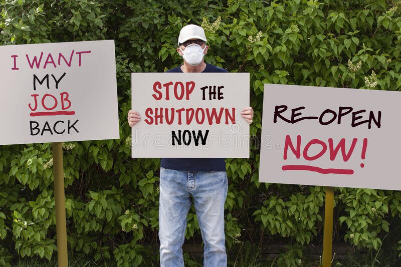 Protester with cap and medical protection mask demonstrate against stay-at-home orders due to the COVID-19 pandemic. With sign saying Stop the Shutdown Now stock photos