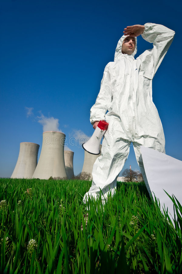 Protester at Nuclear Plant. Protester in protective clothing with a megaphone, standing in a flowering field in the foreground of a nuclear power plant stock photo