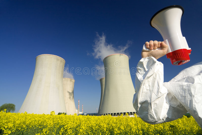 Protester at Nuclear Plant. Nuclear power plant cooling towers at the end of a flowering field, partial view of a protester on the far right holding up a royalty free stock images