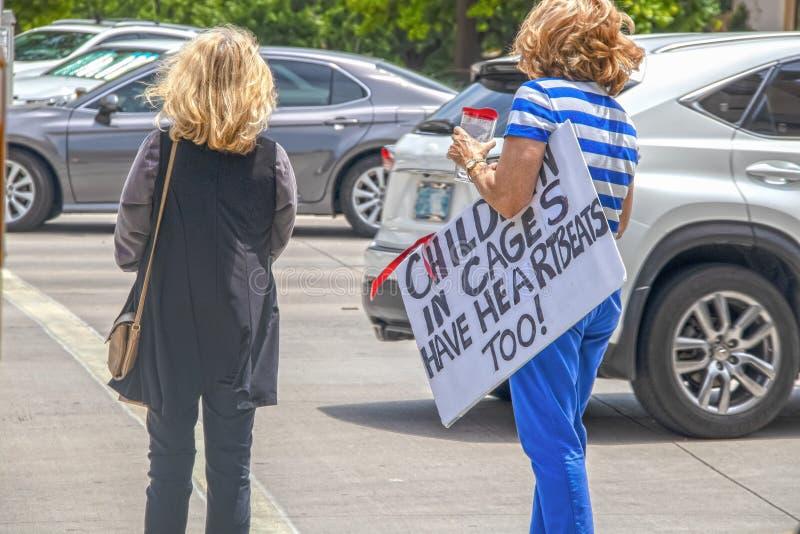Protestera ungar i burar - invandringfrågor - två unidentifiable kvinnapersoner som protesterar korsar den upptagna gatan - ett b arkivbild