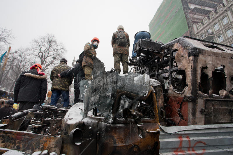 Protesters with hidden faces guard on the top of burned and smashed buses on winter street during anti-government protest stock image