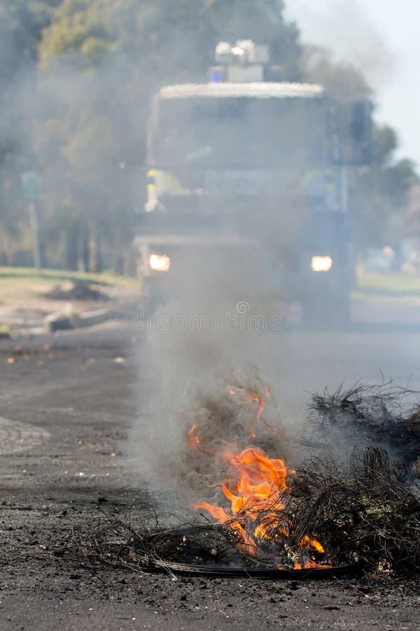 Protesthandling med brinnande däck i väg royaltyfri bild
