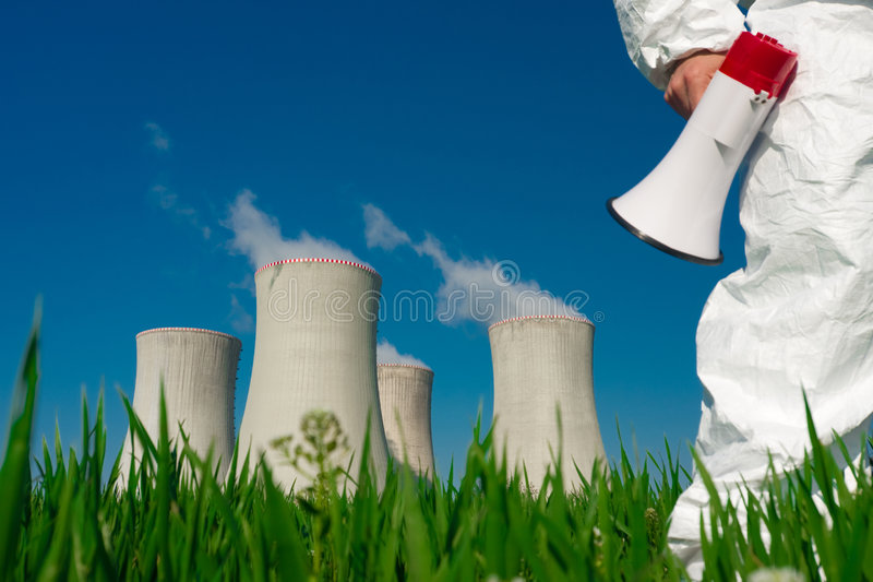 Protesting at Nuclear Plant. Protester in protective clothes carrying a megaphone, in a field in front of the cooling towers of a nuclear power plant stock image