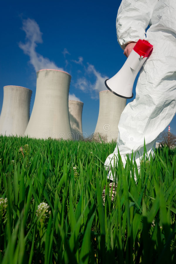 Protesting at Nuclear Plant. Protester in protective clothes carrying a megaphone, in a field in front of the cooling towers of a nuclear power plant stock images