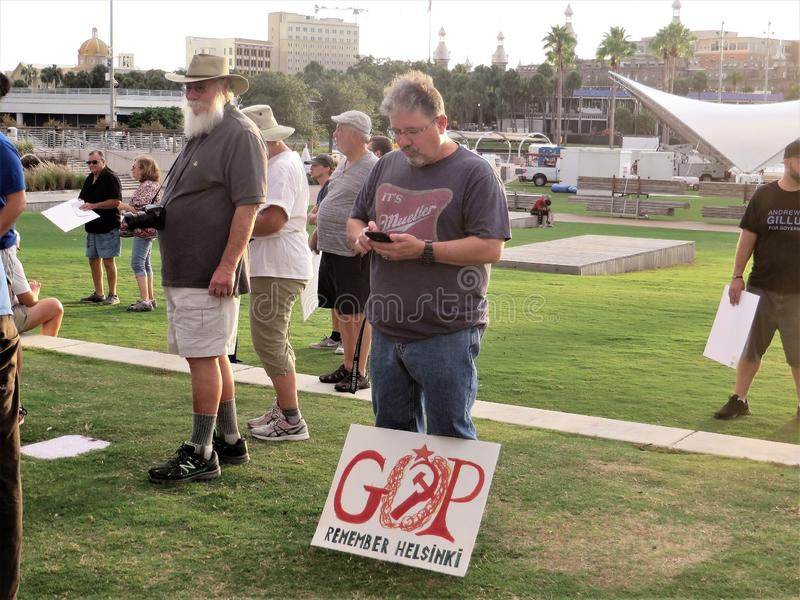 Protestor with signs. Man with homemade red GOP Remember Helsinki sign checks phone messages while protesting flag at MoveOn.org organized demonstration against royalty free stock photography
