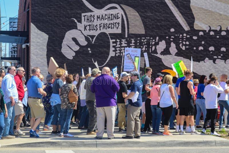 Protestors chodzą za Drewnianym Guthrie malowidłem ściennym który mówi Ten maszyn zwłok faszystów n Tulsa Oklahom usa 3 24 2018 fotografia royalty free