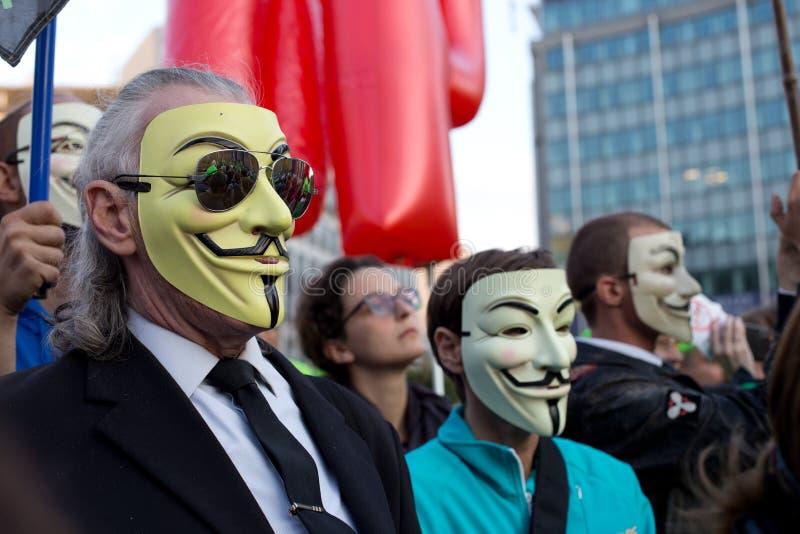 Protestors que llevan los maskes de Guy Fawkes durante la manifestación contra los acuerdos comerciales TTIP y CETA en Bruselas foto de archivo