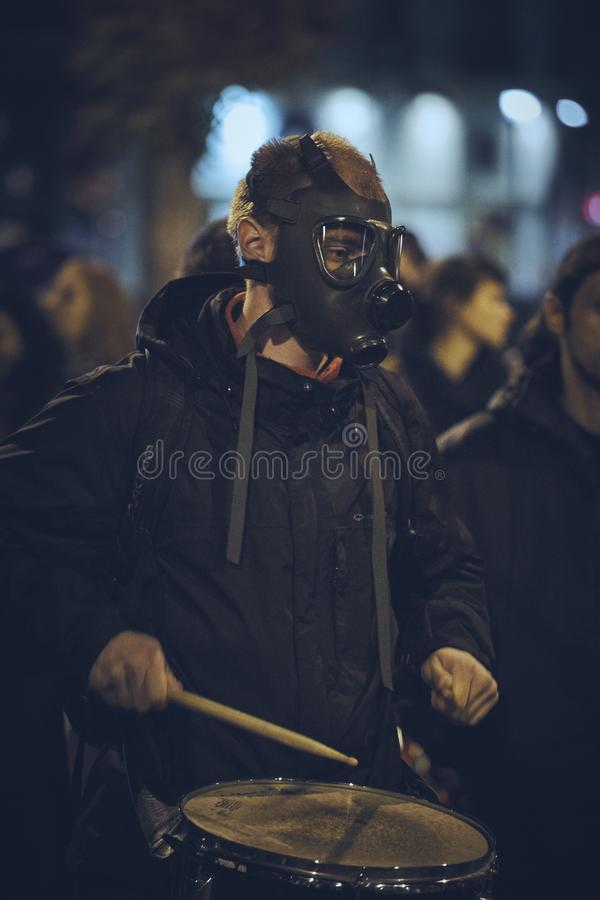 Protests against Rosia Montana gold mine, Bucharest, Romania. Bucharest, Romania - October 6, 2013: Young man wearing gas mask plays the drum during the rally royalty free stock photos