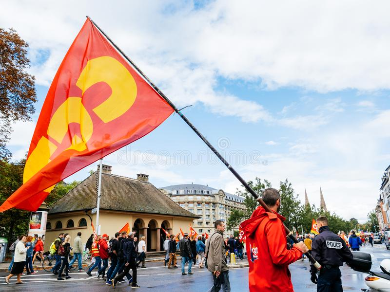 Protests in France against Macron Reforms man with SGT flag. STRASBOURG, FRANCE - SEP 12, 2018: Central street with man waving CGT flag on street during a French royalty free stock image