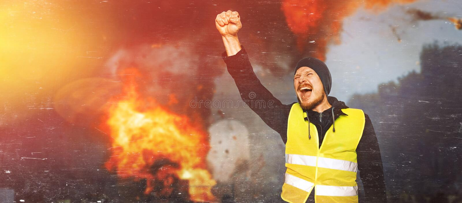 Protests yellow vests. Man raised his hand into a fist and shouted in street. Concept of revolution and protest, the struggle for royalty free stock image