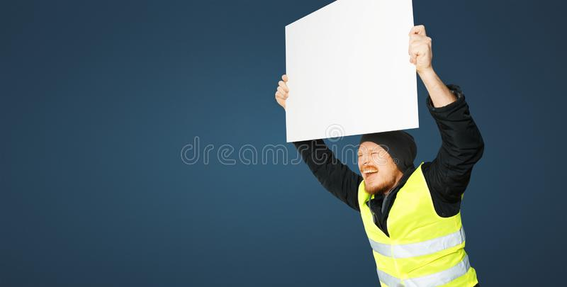 Protests yellow vests. Young man is holding poster. Concept of revolution and protest on blue background. Protests yellow vests. A young man is holding a poster stock photo