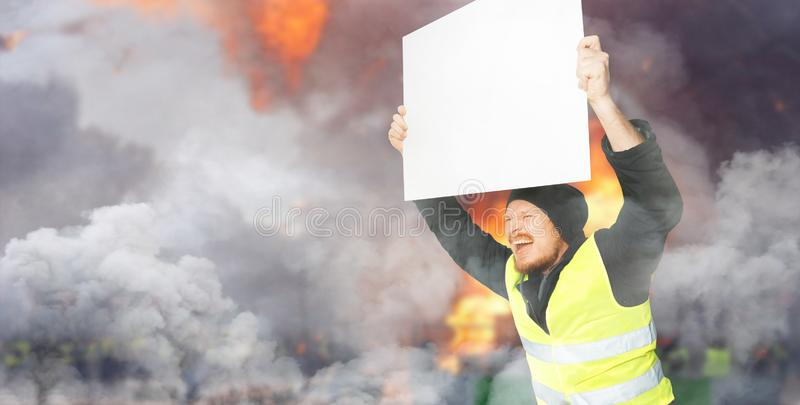 Protests yellow vests. A young man is holding a poster on street. Concept of revolution and protest, the struggle for equal rights. Protests yellow vests. A stock images