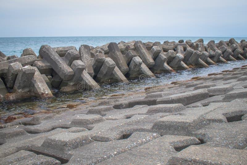 Protezione costiera del frangiflutti costruita dai blocchetti prefabbricati del cemento per ridurre l'intensità di azione dell'on fotografie stock