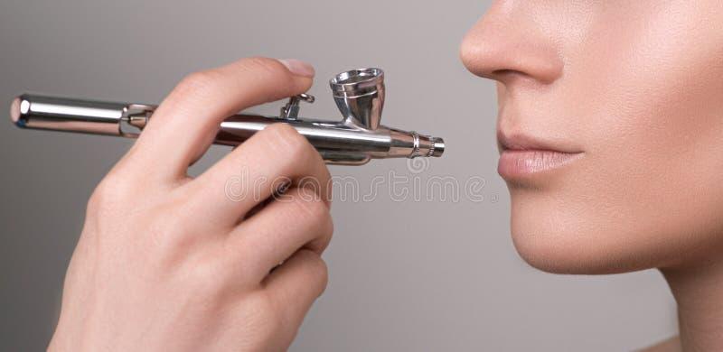 Protezione del labbro Componga con la spazzola di aria Labbra sane della giovane donna Bocca di modello femminile con trucco nudo immagini stock libere da diritti