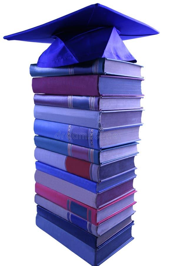 Cappuccio di graduazione sopra il mucchio del libro fotografia stock libera da diritti