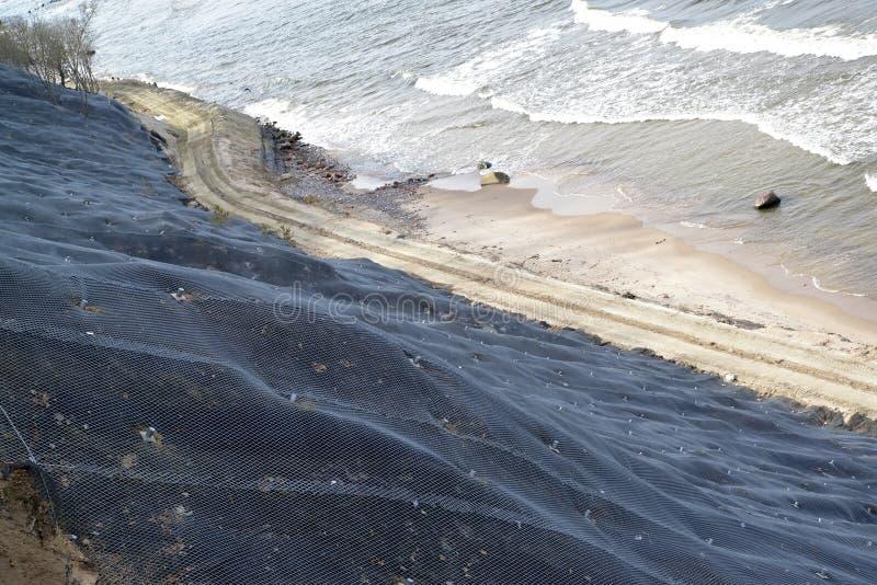 Protezione di ingegneria di un pendio della frana con il rinforzo della maglia con l'ancoraggio sulla spiaggia immagini stock