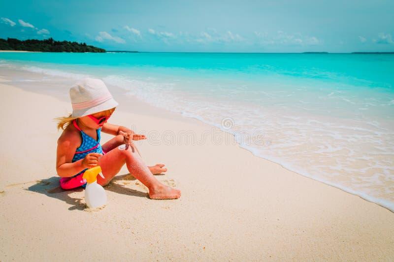 Protezione di Sun - bambina con suncream alla spiaggia immagini stock