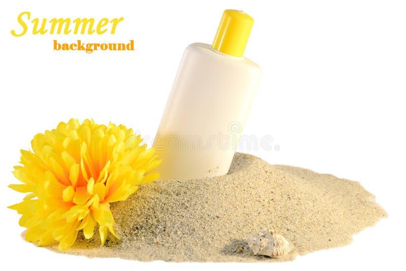 Protezione solare e fiore sulla sabbia fotografia stock