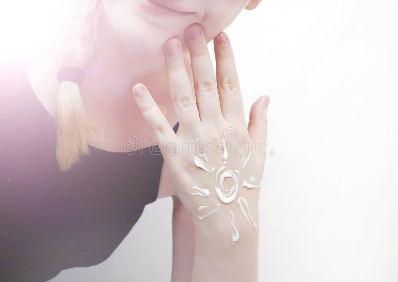 Protezione solare sulla mano sotto forma di sole e di sorriso Crema per le mani, crema di nutrizione, cura personale, idratante fotografie stock