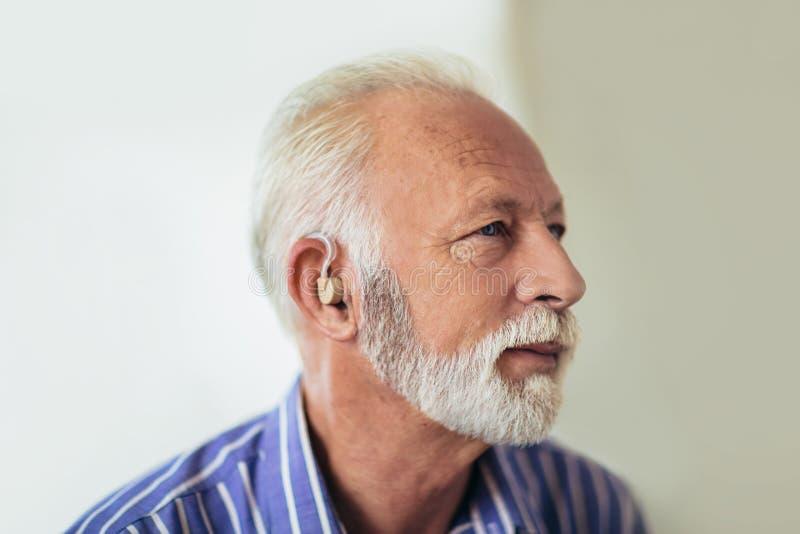Prothèse auditive de port d'homme supérieur photo libre de droits