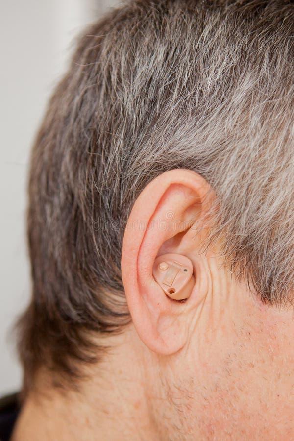 Prothèse auditive moderne en gros plan de Digital dans l'oreille du vieil homme âgé images stock